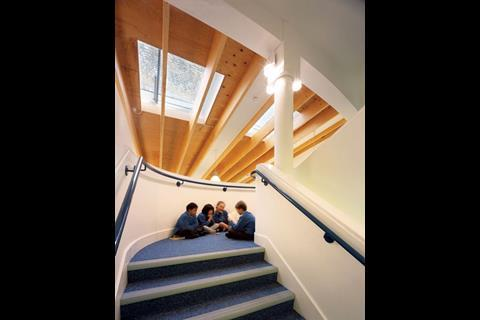 The central library, dog-leg staircase and other classrooms are all open to the laminated-timber roof beams and skylights